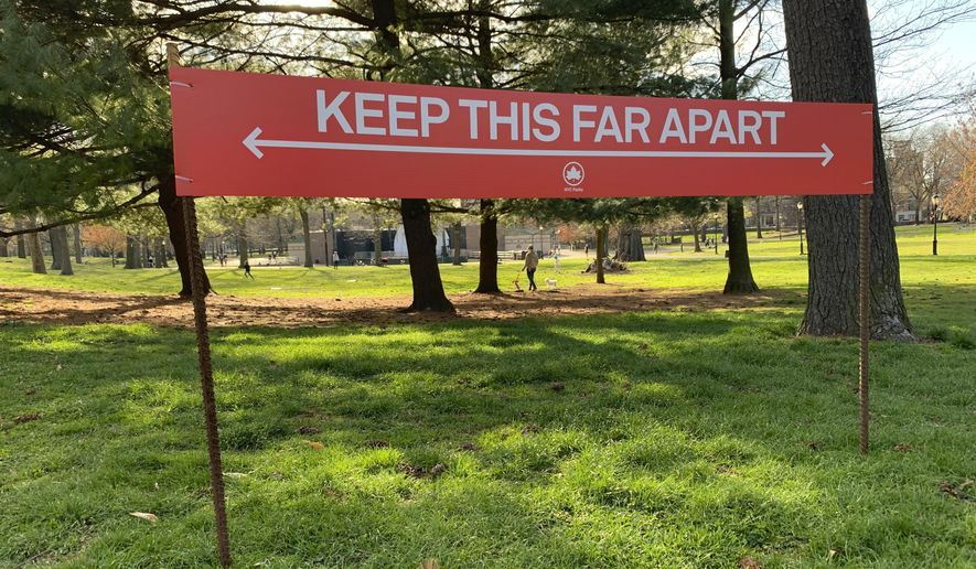 """Signage urging social distancing is seen in Prospect Park in the Brooklyn borough of New York, Wednesday, April 8, 2020. While New York Gov. Andrew Cuomo said New York could be reaching a """"plateau"""" in hospitalizations, he warned that gains are dependent on people continuing to practice social distancing. (AP Photo/Wong Maye-E)"""