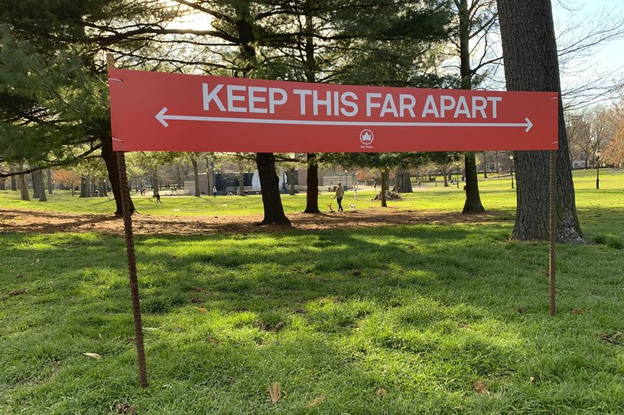 "Signage urging social distancing is seen in Prospect Park in the Brooklyn borough of New York, Wednesday, April 8, 2020. While New York Gov. Andrew Cuomo said New York could be reaching a ""plateau"" in hospitalizations, he warned that gains are dependent on people continuing to practice social distancing. (AP Photo/Wong Maye-E)"