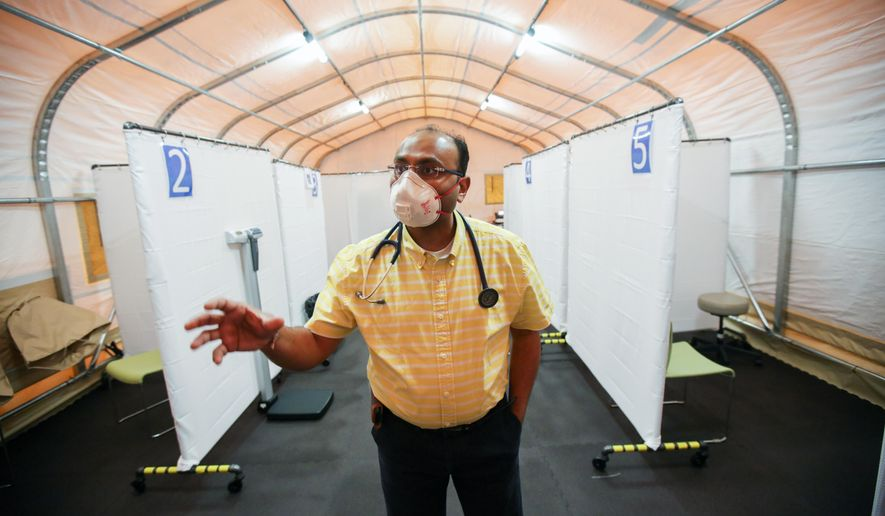 Dr. Jignesh Sheth, chief medical officer for The Wright Center, explains the workings of a new negative pressure tent to triage patients with possible coronavirus infections in Jermyn. Pa., Wednesday, April 8, 2020. The military style tent cycles air out about 15 times an hour to help stop the disease from spreading. (Jake Danna Stevens/The Times-Tribune via AP)