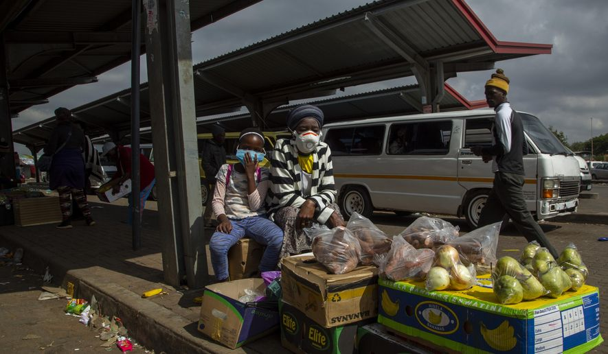 A woman and her daughter wearing face masks to protect against coronavirus, sell fruit and vegetables at the taxi station in Lenasia, south of Johannesburg, South Africa, Wednesday, April 8, 2020. South Africa and more than half of Africa's 54 countries have imposed lockdowns, curfews, travel bans or other restrictions to try to contain the spread of the highly contagious COVID-19 coronavirus. (AP Photo/Themba Hadebe)