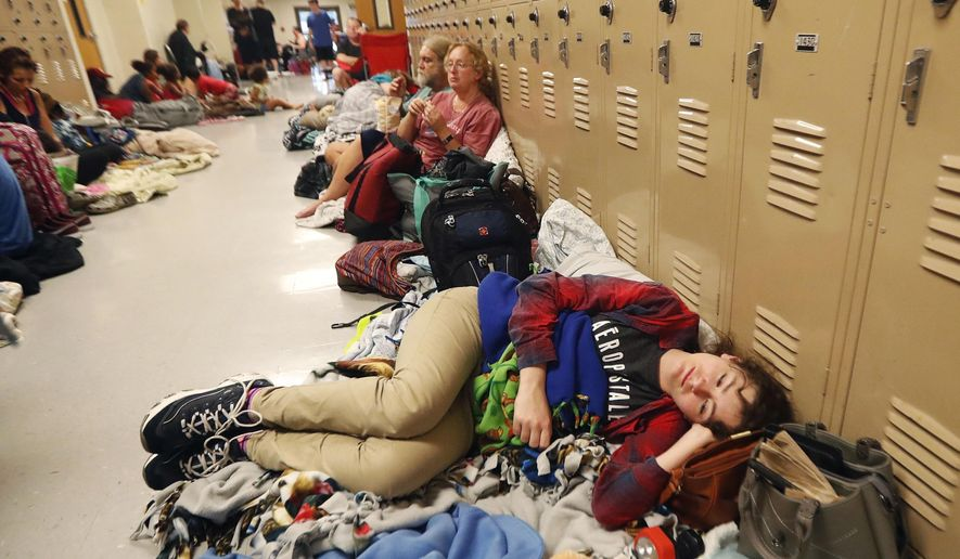 FILE - In this Oct. 10, 2018 file photo, Emily Hindle lies on the floor at an evacuation shelter set up at Rutherford High School, in advance of Hurricane Michael, in Panama City Beach, Fla. As each day brings the United States closer to peak severe weather season, Tornado Alley residents are facing a difficult question: Is it better to take on a twister outside a community shelter or to face the possibility of contracting the new coronavirus inside one?  (AP Photo/Gerald Herbert, File)