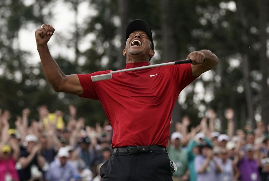 In this April 14, 2019, file photo, Tiger Woods reacts as he wins the Masters golf tournament at Augusta National in Augusta, Ga. It was voted the third best Masters. Woods blazing to victory in his Sunday red at the Masters, a scene once so familiar, was never more stunning.  (AP Photo/David J. Phillip, File)  **FILE**