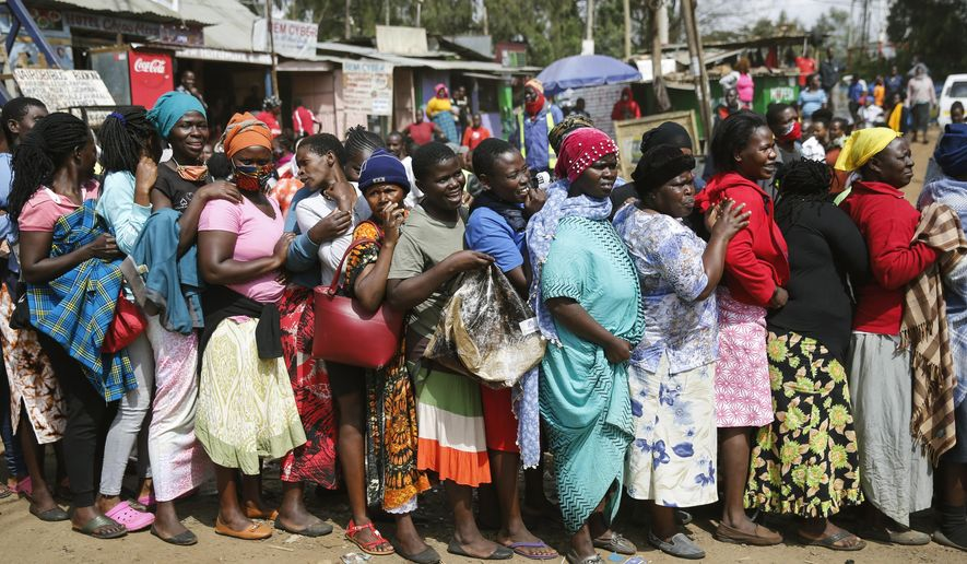 Women queue for a planned distribution of food for those suffering under Kenya's coronavirus-related movement restrictions, before the crowd pushed through a gate and created a stampede, causing police to fire tear gas and leaving several injured, at a district office in the Kibera slum, or informal settlement, of Nairobi, Kenya, Friday, April 10, 2020. (AP Photo/Brian Inganga)