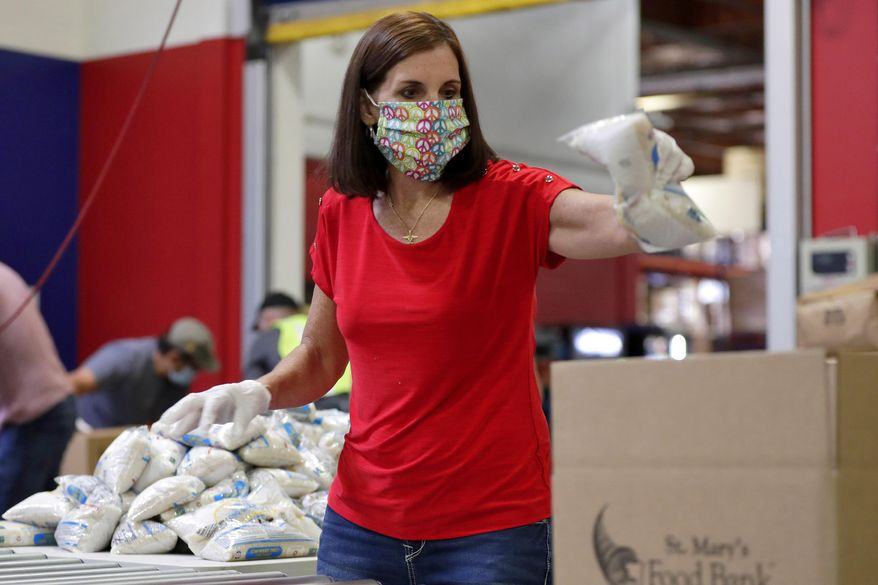 U.S. Sen. Martha McSally, R-Ariz., packs food boxes at St. Mary's Food Bank Friday, April 10, 2020, in Phoenix. Arizona. McSally is pinning the blame for the coronavirus outbreak on China and the World Health organization, while her likely Democratic rival, Mark Kelly, is pushing President Donald Trump to more aggressively force U.S. companies to produce medical supplies. (AP Photo/Matt York)