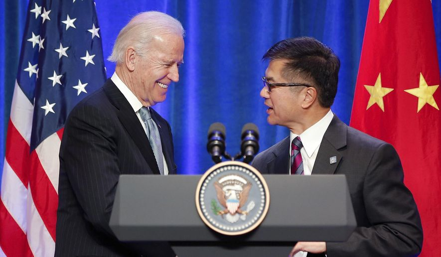 FILE - In this Dec. 5, 2013, file photo, then-Vice President Joe Biden, left, shakes hands with U.S. Ambassador to China Gary Locke during a business leaders breakfast at The St. Regis Beijing hotel in Beijing. Locke is denouncing President Donald Trump for a new campaign ad that seems to falsely imply Locke was a Chinese official. Trump's reelection campaign released an ad that accused Biden, the presumptive Democratic presidential nominee, of being too cozy with China. It featured an image of Biden and Locke on a stage with U.S. and Chinese flags in the background. (AP Photo/Lintao Zhang, Pool)