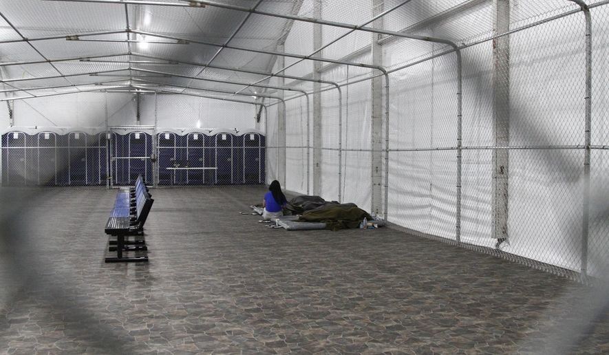 in this Aug. 15, 2019, file photo, migrants are detained in a tented, air-conditioned cage at a Border Patrol detention facility in Tornillo, Texas.  (AP Photo/Cedar Attanasio File) **FILE**