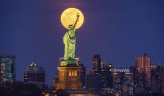 In this March 9, 2020, photo, the full moon rises behind the Statue of Liberty in New York. From California to Colorado to Georgia and New York, Americans are taking a moment each night at 8 to howl to thank the nation's health care workers and first responders for their selfless sacrifices during the coronavirus pandemic. (AP Photo/J. David Ake, File)