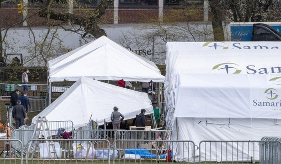In this March 31, 2020 photo, a Samaritan's Purse crew erects privacy tents at a 68 bed emergency field hospital specially equipped with a respiratory unit in New York's Central Park, in New York. International charity groups which usually provide support to war-torn or impoverished countries are now sending humanitarian aid to some of the wealthiest places in the United States to help manage the coronavirus pandemic.  (AP Photo/Mary Altaffer)