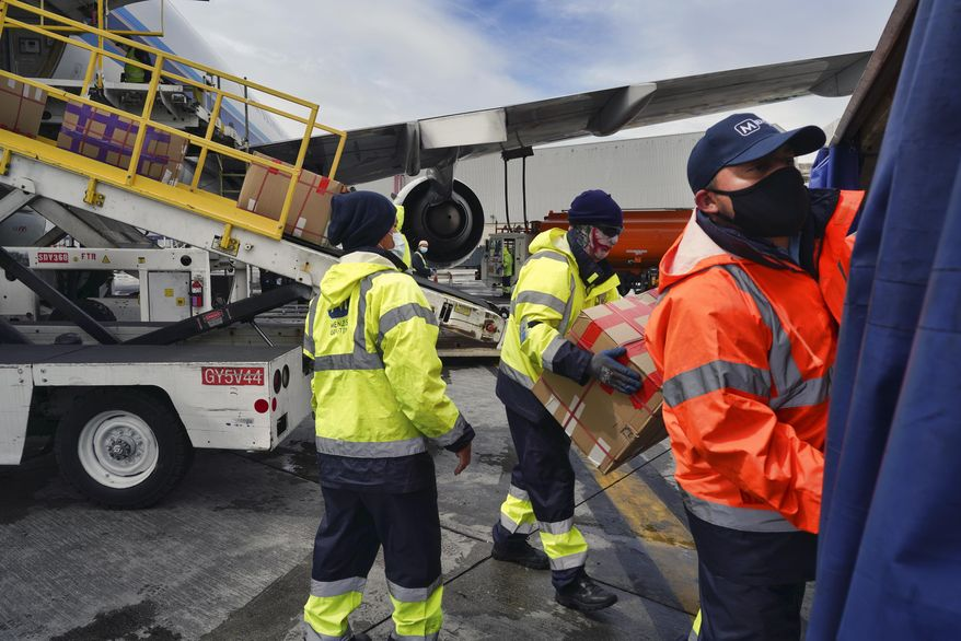 Wearing protective masks ground crew at the Los Angeles International airport unload supplies of medical personal protective equipment, PPE, from a China Southern Cargo plane upon it's arrival on Friday, April 10, 2020. (AP Photo/Richard Vogel)