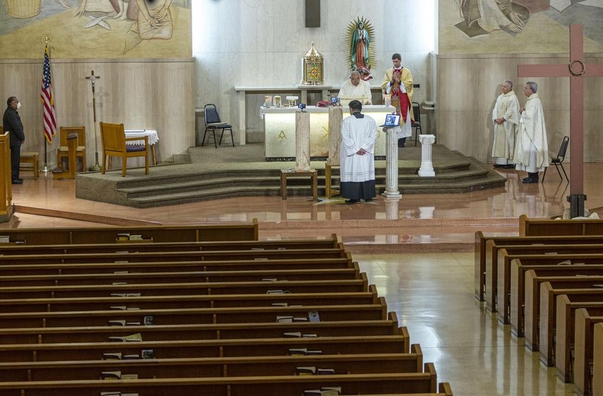 The Mass of the Lord's Supper is live-streamed from St. Anthony Parish in San Gabriel, Calif., Thursday, April 9, 2020, with no parishioners present. Without the ability to have public Mass and visitors due to the new coronavirus pandemic, the parish live-streams its services. (AP Photo/Damian Dovarganes)