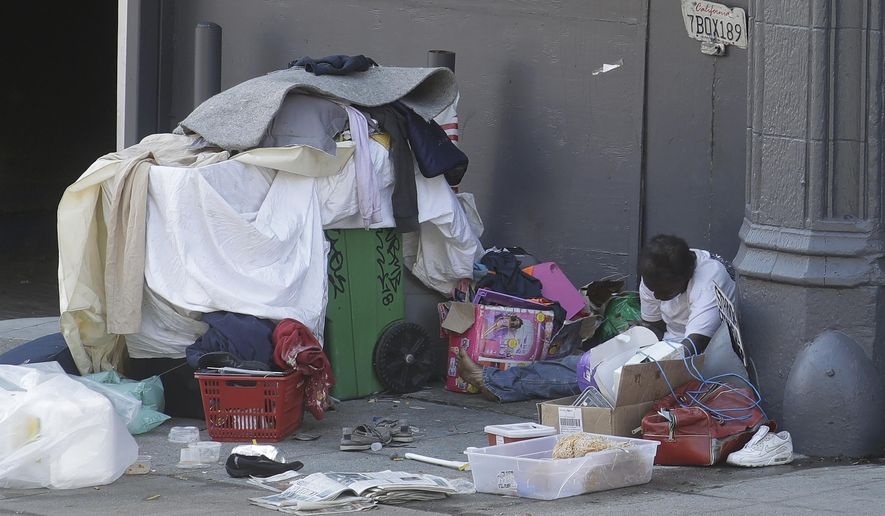 FILE - In this April 2, 2020, file photo, a homeless person sits on the street in San Francisco. San Francisco's mayor reported Friday, April 10, 2020, that 70 people at the city's largest homeless shelter have tested positive for COVID-19, infuriating advocates of the homeless who have been pushing the city for weeks to get people out of crowded shelters and into individual hotel rooms. (AP Photo/Jeff Chiu, File)