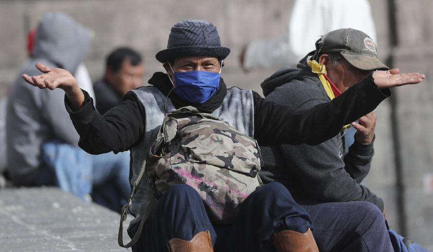 """A man gestures to the camera as he rests in a public square in Quito, Ecuador, Friday, April 10, 2020. The government declared a """"health emergency"""" amid the new coronavirus pandemic, restricting movement to only those who provide basic services, enacting a curfew  and closing schools. (AP Photo/Dolores Ochoa)"""