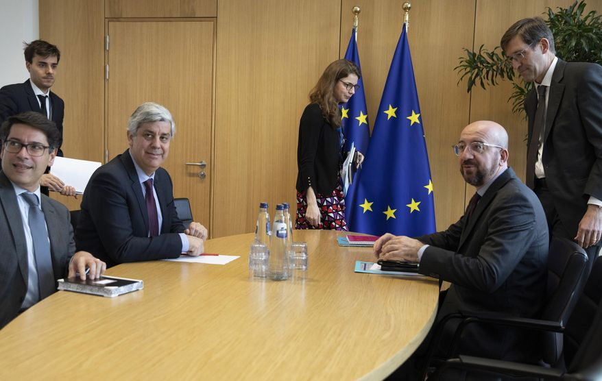 In this Tuesday, Feb. 18, 2020, file photo Eurogroup President and Portugal's Finance Minister Mario Centeno, third left, meets with European Council President Charles Michel, second right, at the Europa building in Brussels. (AP Photo/Virginia Mayo, Pool, File)
