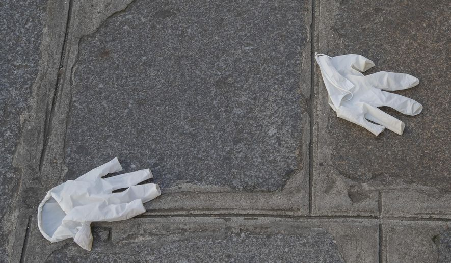 Plastic gloves lays on the ground in Paris, Friday, April 10, 2020, during a nationwide confinement to counter the new coronavirus. For most people, the new coronavirus causes only mild or moderate symptoms, such as fever and cough. For some, especially older adults and people with existing health problems, it can cause more severe illness, including pneumonia. (AP Photo/Michel Euler)