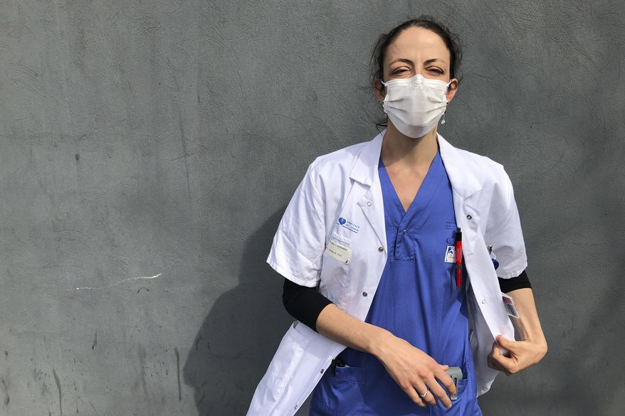 In this photo taken on Tuesday, April 7, 2020, Aurelie Gouel, an ICU doctor, poses during a break in her shift treating COVID-19 patients at Bichat Hospital in Paris. Gouel was infected by the new coronavirus in March but rushed back to work as soon as she recovered from her high fever, cough and other symptoms because she felt compelled to rejoin the fight to save lives.  The coronavirus has infected so many doctors, nurses and other health workers that some are now returning to work hoping that they are now armed with some degree of immunity. (AP Photo/John Leicester)
