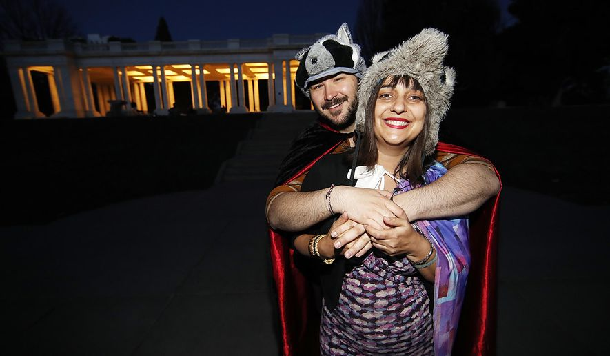 In this Wednesday, April 8, 2020, photograph, Brice Maiurro, back, hugs Shelsea Ochoa after they led a howl in Cheesman Park in Denver as a statewide stay-at-home order remained in effect in an effort to reduce the spread of the coronavirus.  (AP Photo/David Zalubowski)
