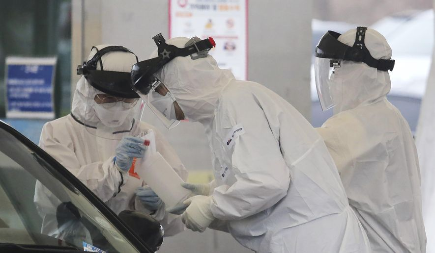 FILE - In this March 1, 2020 file photo, medical staff wearing protective suits take samples from a person with suspected symptoms of the new coronavirus at a drive-thru virus test facility in Goyang, South Korea. When the first cases of the disease showed up in South Korea, they reacted quickly with the use of widespread testing, technology to trace at-risk groups, and strict social quarantines and distancing. (AP Photo/Ahn Young-joon, File)