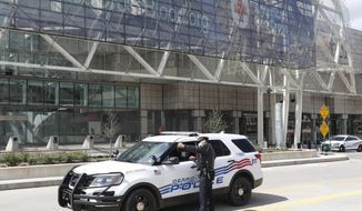 """Detroit Police Capt. Jevon Johnson talks with Lt. Pride Henry outside the TCF Center, Friday, April 10, 2020, in Detroit. Johnson, 44, was quarantined for a little less than week after developing a cough and being exposed to another officer who tested positive for the coronavirus. About 10 to 13 minutes after taking the Abbott Labs nasal swab test Johnson was told he didn't have COVID-19. """"That was a weight off my mind,"""" the 21-year police veteran said. """"Our medical subunit was able to return me to work immediately."""" (AP Photo/Carlos Osorio)"""