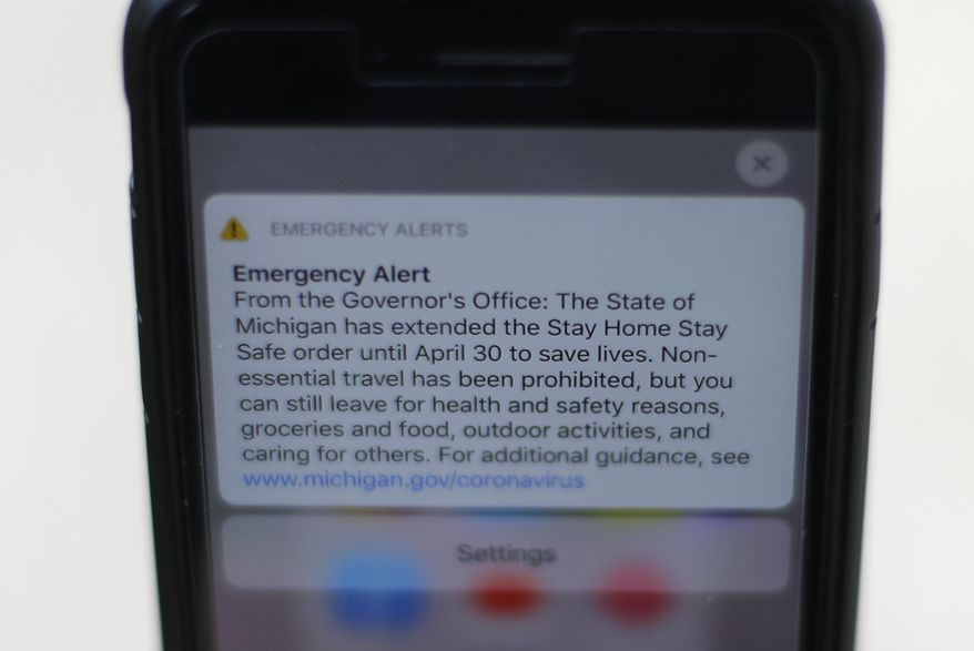 An Emergency Alert from the Michigan Governors office is shown on a cellular phone in Detroit, Thursday, April 9, 2020. Gov. Gretchen Whitmer extended the Stay Home Safe order until April 30 to save lives from the new coronavirus COVID-19. (AP Photo/Paul Sancya)