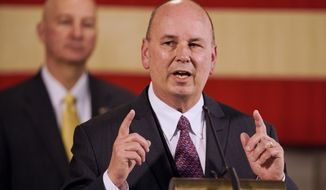 Neb. Gov. Pete Ricketts, rear, listens as Scott Frakes, director of the Nebraska Department of Correctional Services, speaks during a news conference in Lincoln, Neb., Friday, April 10, 2020, on developments in the struggle against the coronavirus. (AP Photo/Nati Harnik)