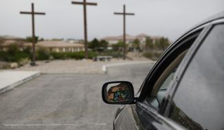 Patty Duffey, wearing a mask, stops at a station at a drive-thru Stations of the Cross for social distancing due to the coronavirus on Good Friday at the New Song Church, Friday, April 10, 2020, in Henderson, Nev. (AP Photo/John Locher)