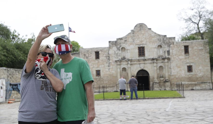 Visitor wear face masks as they take a selfie in front to the Alamo, which is closes due to the COVID-19 outbreak, in San Antonio, Friday, April 10, 2020. San Antonio remains under stay-at-home orders due to the COVID-19 outbreak keeping tourist areas closed to the public.(AP Photo/Eric Gay)