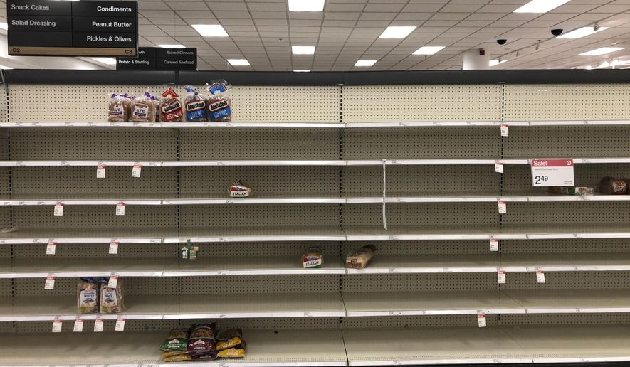 Shelves usually stocked with bread lay nearly empty at a Target in Abington, Pa., Wednesday, March 18, 2020. Coronavirus concerns have led to consumer panic buying of grocery staples. (AP Photo/Matt Rourke)