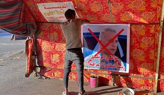 "A poster with a defaced picture of Mustafa Kadhimi, Iraq's intelligence chief and new prime minister-designate, is pictured in Tahrir Square, Baghdad, Iraq, Saturday, April 11, 2020. The Arabic sentence on the poster reads ""an American citizen is the head of the Iraqi intelligence.""(AP Photo/Khalid Mohammed)"