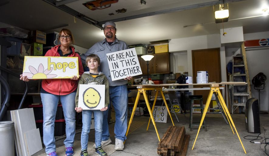 "Cyndy and Scott Huber make signs with encouraging words on them on Thursday, April 2, 2020 in their garage in Sioux Falls, S.D. The couple along with their grandson, Koi Retting, 8, decided to make ""Signs for the times"" for people to take for free and display in their own yards. (Abigail Dollins/The Argus Leader via AP)"