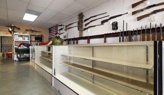 In this Monday, April 6, 2020, file photo, Elite Firearms sales associate Joe Potter stands behind empty gun shelves in Las Vegas. Potter says he ran 475 firearm background checks in a three-week period. (Wade Vandervort/Las Vegas Sun via AP) ** FILE **
