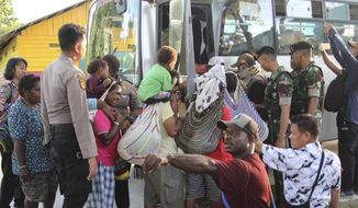 In this Friday, March 6, 2020 photo, villagers board a bus as they flee their homes following clashes between security forces and a rebel group, in Tembagapura, Papua, Indonesia. The attacks between gunmen and security forces near the world's largest gold mine in Indonesia's easternmost region has caused nearly 2,000 villagers to flee, officials said Saturday. (AP Photo/Sevianto Pakiding)