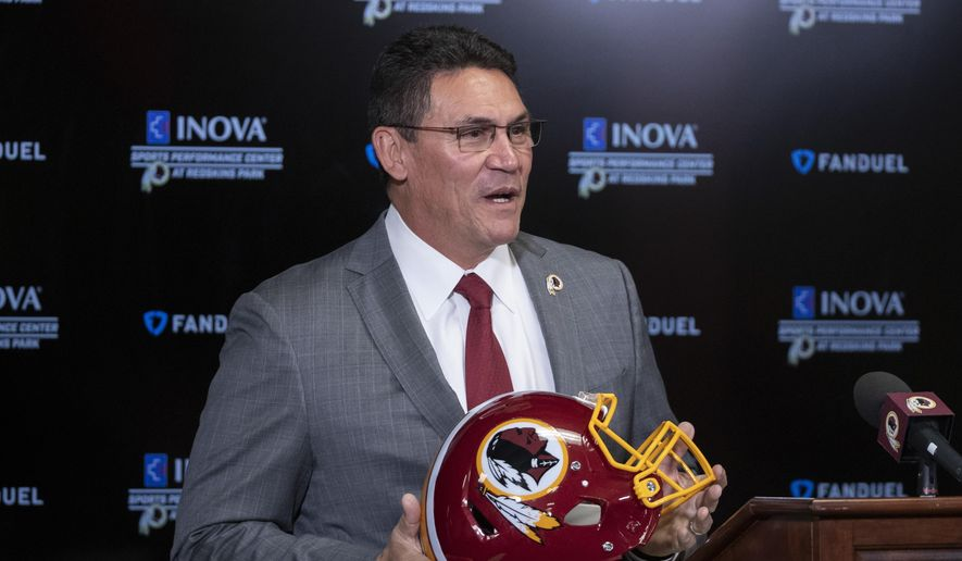 In this Jan. 2, 2020, file photo, Washington Redskins new head coach Ron Rivera holds up a helmet during a news conference at the team's NFL football training facility in Ashburn, Va. The new Redskins coach took some big swings in free agency but has so far been more focused on incremental additions and subtractions to change the culture within the organization and build for the future. (AP Photo/Alex Brandon)  ** FILE **
