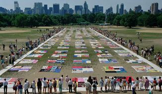 FILE - In this Saturday, June 25, 1988 file photo, people watch as almost 1,500 quilt panels bearing the names of New York area residents who have died of AIDS are unfolded on the Great Lawn in New York's Central Park. The panels, which are expected to be incorporated into the national Names Project AIDS Quilt, include 75 bearing the names of metropolitan area infants. (AP Photo/Wilbur Funches, File)