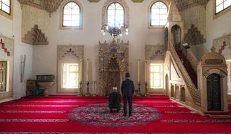 In this Thursday, April 9, 2020 photo two clerics pray inside the 16th century built Gazi Husrev-beg Mosque in Sarajevo, Bosnia, as worshipers stay away due to the national lockdown the authorities have imposed attempting to limit the spread of the new coronavirus. (AP Photo/Kemal Softic)