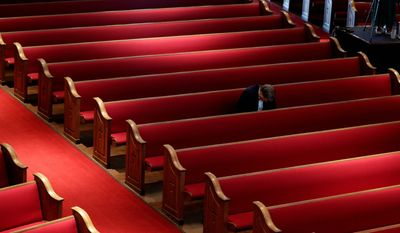 A man prays in a mostly empty Easter service in San Antonio on Sunday.