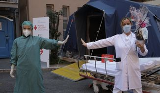 Monica Carfora, right, deputy head of the emergency of the Santo Spirito Hospital, which now has a separate emergency for possible covid patients, holds a chocolate Easter egg as she poses for a photograph with nurse Silvia Sforza, holding out their arms to indicating social distancing, outside the entrance to for covid emergency, in central Rome, Sunday, April, 12, 2020. The new coronavirus causes mild or moderate symptoms for most people, but for some, especially older adults and people with existing health problems, it can cause more severe illness or death. (AP Photo/Alessandra Tarantino)