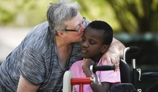 In this Thursday, March 26, 2020 photo, Tori Wentz, left, gives her son Ricky, 11, who is blind, deaf and intellectually disabled, a kiss outside their West Knoxville, Tenn. home.  A former nurse, Wentz adopted Ricky, a native of Ghana, six years ago. (Caitie McMekin/The Tennessean via AP)