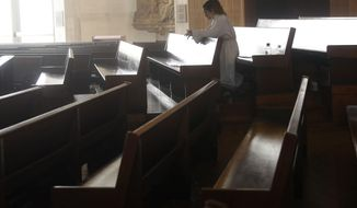 A choir member celebrates Easter Mass, which was live streamed, at a nearly empty St. Mary's Cathedral in San Francisco, Sunday, April 12, 2020. Christians around the world are celebrating Easter at a distance, with many churches closed and family gatherings canceled amid wide-ranging shutdowns due to the coronavirus pandemic. (AP Photo/Jeff Chiu)
