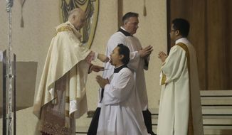 San Francisco Archbishop Salvatore Cordileone, left, gives communion while celebrating Easter Mass, which was live streamed, at St. Mary's Cathedral in San Francisco, Sunday, April 12, 2020. Christians around the world are celebrating Easter at a distance, with many churches closed and family gatherings canceled amid wide-ranging shutdowns due to the coronavirus pandemic. (AP Photo/Jeff Chiu)  ** FILE **
