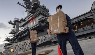 In this April 7, 2020, photo released by the U.S. Navy, sailors assigned to the aircraft carrier USS Theodore Roosevelt move ready to eat meals for sailors who have tested negative for COVID-19 and are being taken to local hotels in an effort to implement social distancing at Naval Base Guam. People in Guam are used to a constant U.S. military presence on the strategic Pacific island, but some are nervous as hundreds of sailors from the coronavirus-stricken Navy aircraft carrier flood into hotels for quarantine. Officials insist they have enforced strict safety measures. (Mass Communication Specialist Julio Rivera/U.S. Navy via AP)