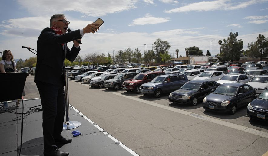 In this file photo, Pastor Paul Marc Goulet speaks to people in their cars at an Easter drive-in service at the International Church of Las Vegas, Sunday, April 12, 2020, in Las Vegas. On Saturday, April 18, a Tennessee mayor confirmed he was reversing course and would allow drive-in church services during the coronavirus pandemic after his city was sued over its ban. (AP Photo/John Locher) **FILE**