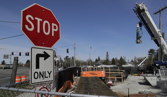 In this April 6, 2020, file photo, equipment and supplies sit staged near a roadwork construction project in Seattle where ramps off of the Highway 520 floating bridge meet Montlake Boulevard that has been shut down due to concern over the spread of the coronavirus. The $2 trillion federal stimulus package enacted in March included billions of dollars for public transit systems, publicly owned commercial airports and Amtrak passenger train service, but earmarked nothing for state highways and bridges. Many of those projects across the country have been put on hold because of a sharp drop in fuel taxes, tolls and user fees since the coronarvirus-related shutdowns suspended much of the U.S. economy. (AP Photo/Ted S. Warren)