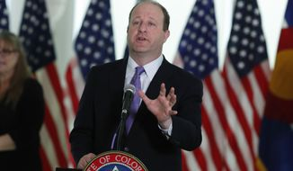 Colorado Gov. Jared Polis makes a point during a news conference to update the state's efforts in battling the spread of the new coronavirus in the governor's mansion Monday, April 13, 2020, in Denver. (AP Photo/David Zalubowski)