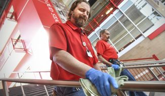 Building services foreman Brian Toutges and lead general maintenance worker Bob Dubbin clean hand railings near the entrance to the Herb Brooks National Hockey Center Wednesday, April 1, 2020, at St. Cloud State University in St. Cloud, Minn. (Dave Schwarz/The St. Cloud Times via AP)