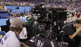 FILE - In this April 2, 2010, file photo, a network television camera is seen during a practice session for the NCAA Final Four college basketball tournament in Indianapolis. Some technicians who work on sports broadcast crews believed their jobs could survive most economic downturns because people still watch sports while the networks that air the games still receive advertising revenues. But they're facing almost unprecedented hardships during the coronavirus pandemic. The pandemic has shut down all sports and put technicians out of work and on unemployment.(AP Photo/Michael Conroy, File)