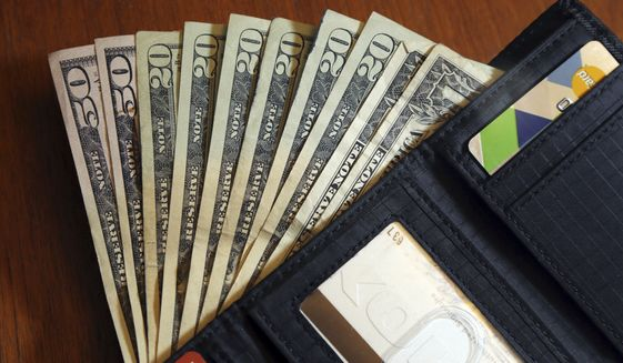 FILE - In this June 15, 2018, file photo, cash is fanned out from a wallet in North Andover, Mass. With lives and finances strained by the novel coronavirus pandemic, now is the time to focus on your money management skills. (AP Photo/Elise Amendola, File)