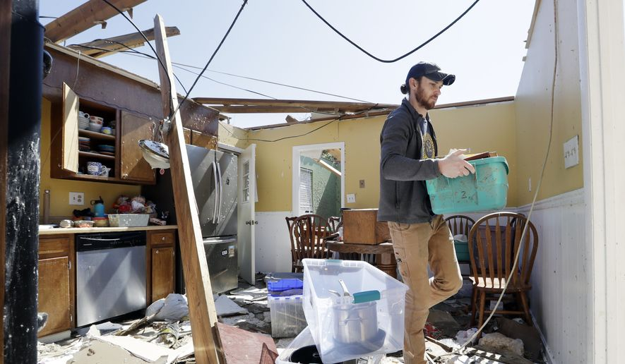 Matthew Alexander carries items through the kitchen of the damaged home of his parents-in-law as he helps to salvage items Tuesday, April 14, 2020, in Chattanooga, Tenn. Tornadoes went through the area Sunday, April 12. (AP Photo/Mark Humphrey)