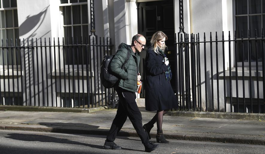 Key adviser to Prime Minister Boris Johnson, Dominic Cummings and his assistant Cleo Watson arrive at London's Downing Street in the dappled early morning sunlight Tuesday April 14, 2020.  Prime Minister Boris Johnson remains in convalescence at his country home of Chequers, following his hospialisation with the coronavirus.  The highly contagious COVID-19 coronavirus has impacted on nations around the globe, many imposing self isolation and exercising social distancing when people move from their homes. (Stefan Rousseau / PA via AP)