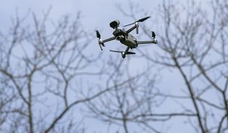 A drone operated by Sgt. Christian Rodriguez hovers at Hubbard Park in Meriden, Conn., Tuesday, April 14, 2020. The drone, which has a speaker attached, is being used to remind visitors to practice social distancing and limit their gatherings in public settings during the coronavirus pandemic. (Dave Zajac/Record-Journal via AP) ** FILE **