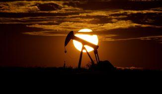 The sun sets behind an idle pump jack near Karnes City, Texas, Wednesday, April 8, 2020, file photo. (AP Photo/Eric Gay)  ** FILE **